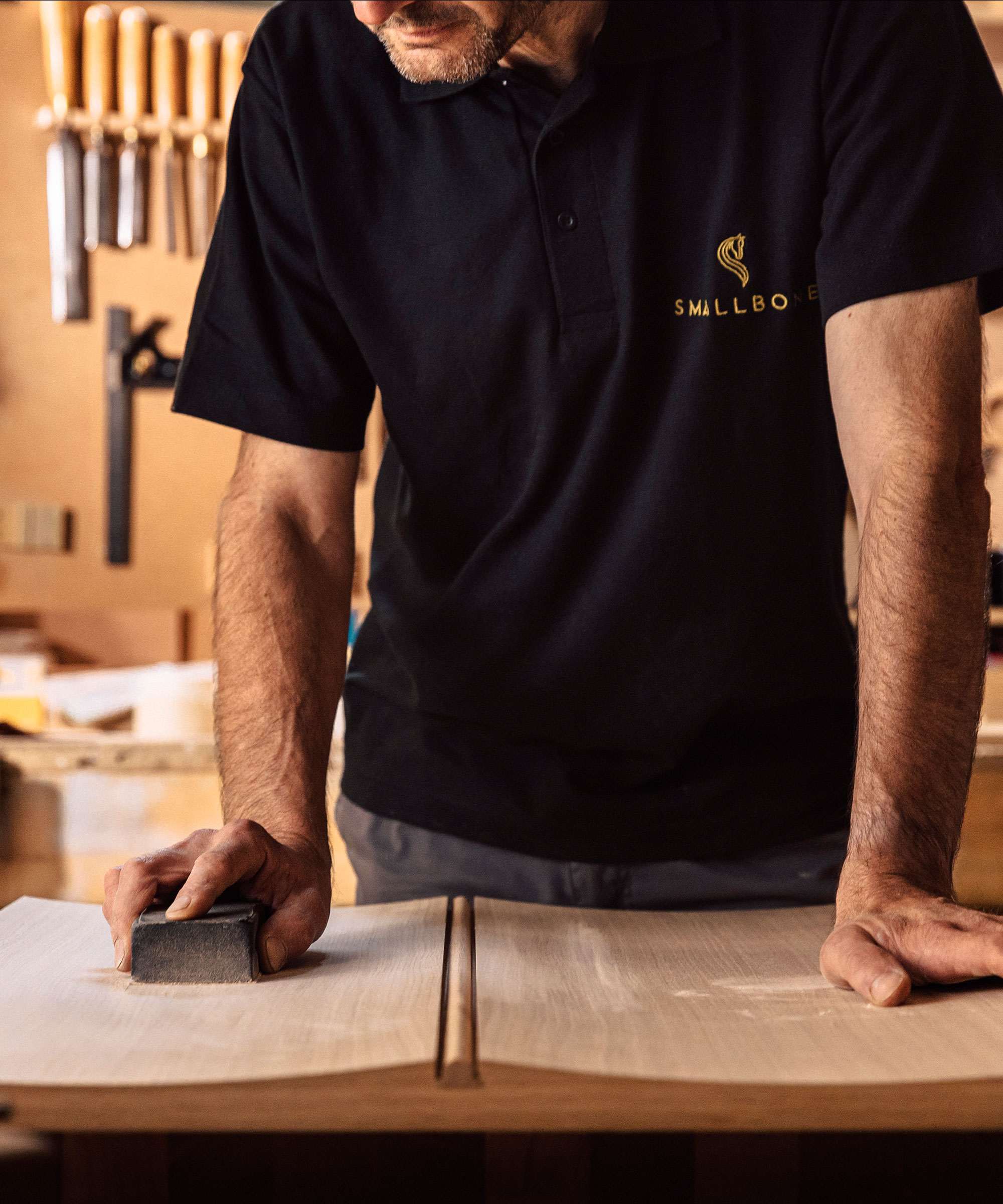 A Smallbone craftsman sanding an Icarus cabinet door front