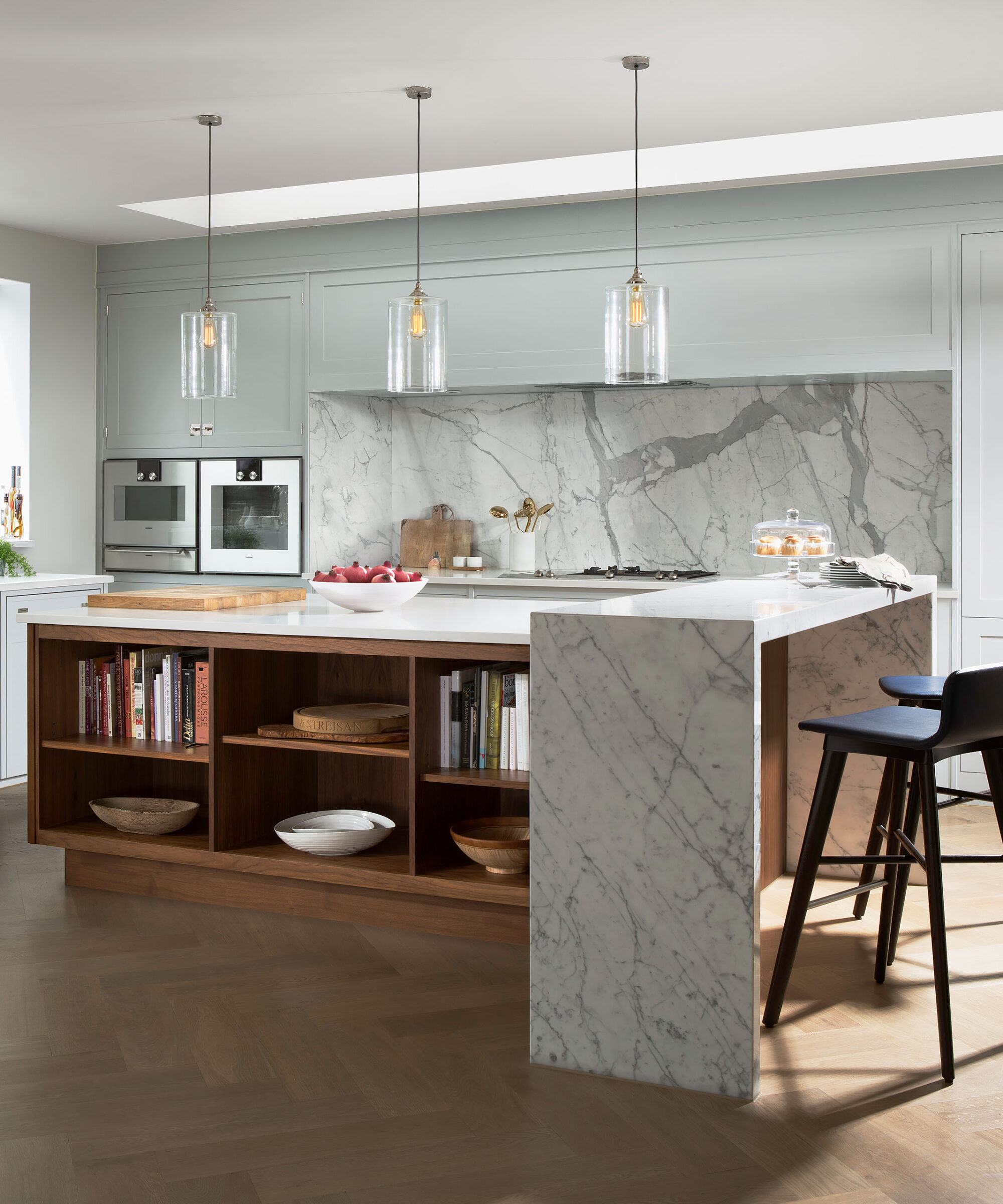 A Smallbone Iconic collection kitchen hand painted in a pale grey-green colour with a natural finish wooden central island with waterfall-edge marble counter