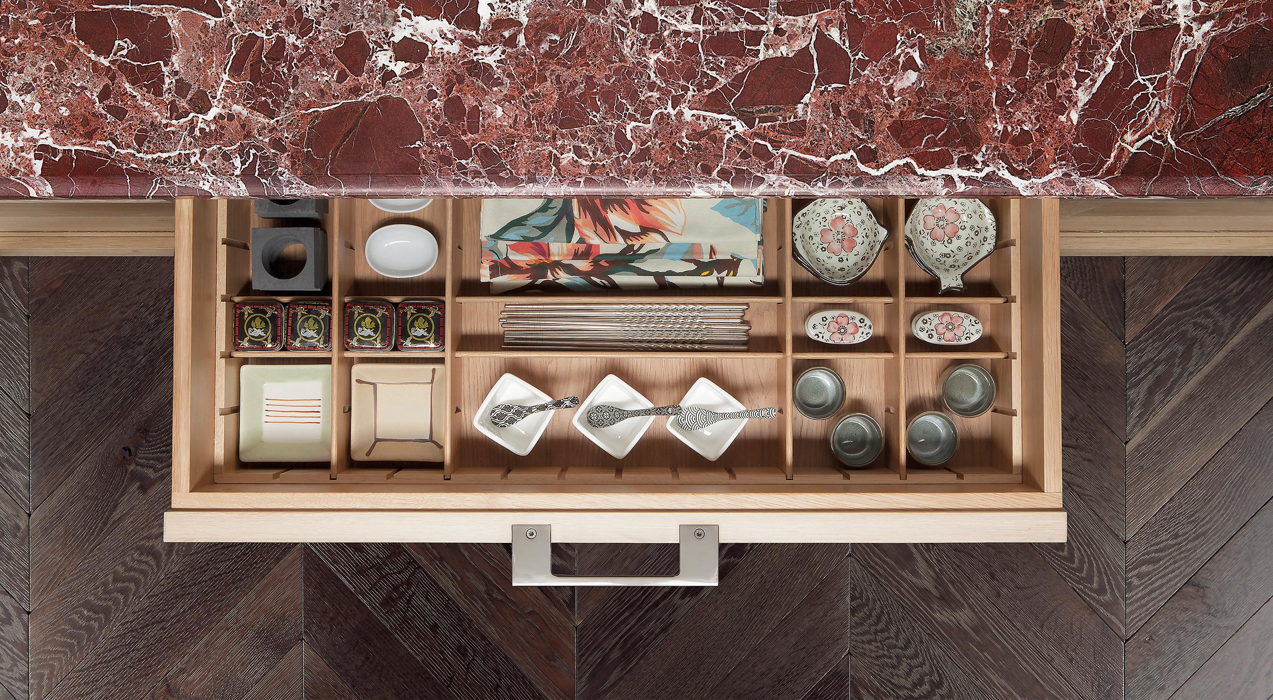 A Smallbone Brasserie kitchen island with limed oak cabinetry and Rosso Levanto marble worktop
