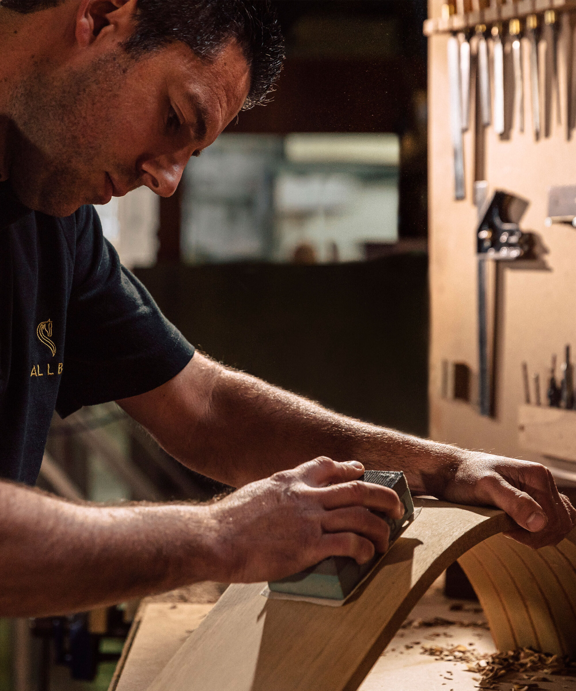 A Smallbone craftsman at his workbench sanding cabinetry