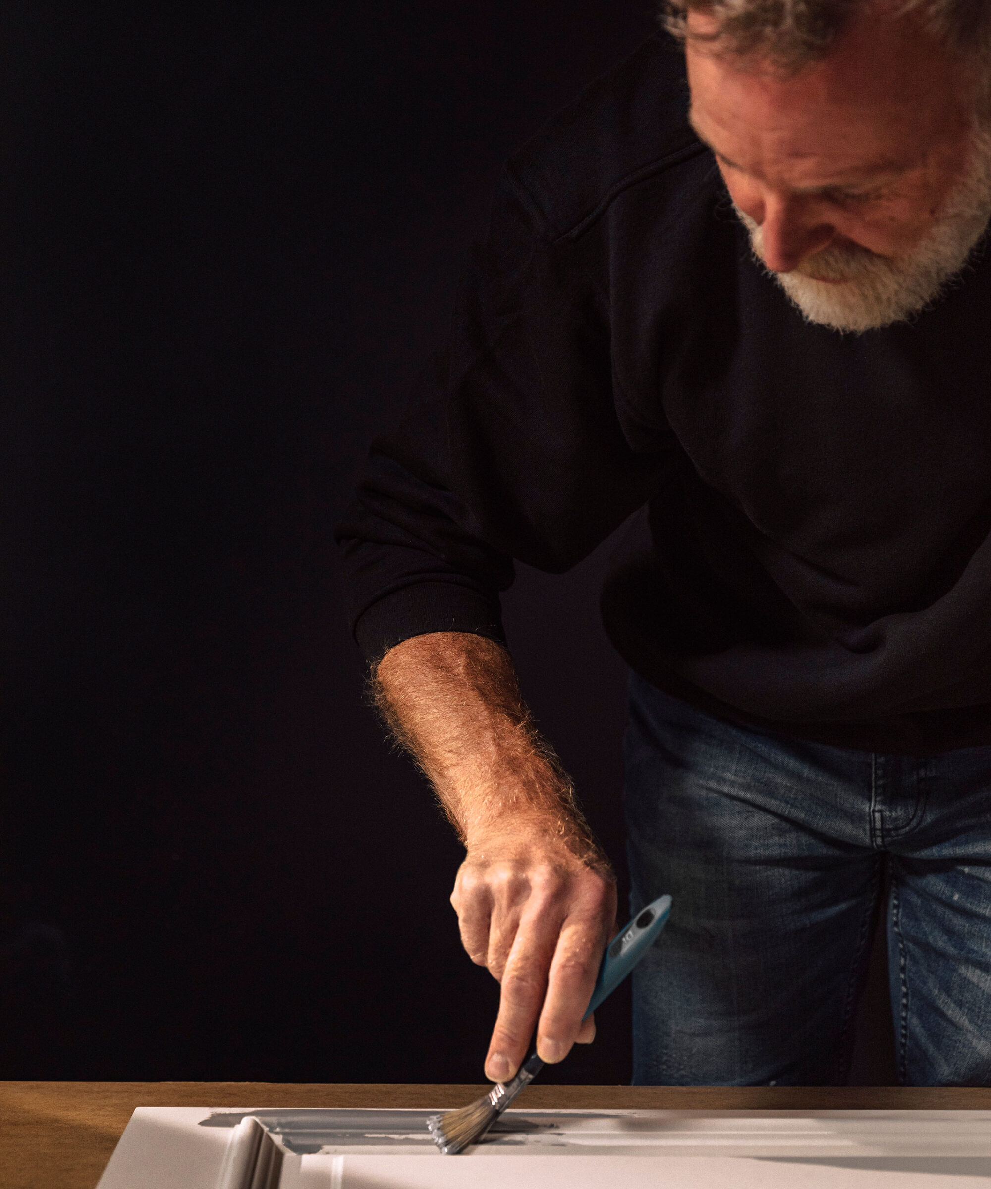 a Smallbone craftsman hand-painting a cabinet front