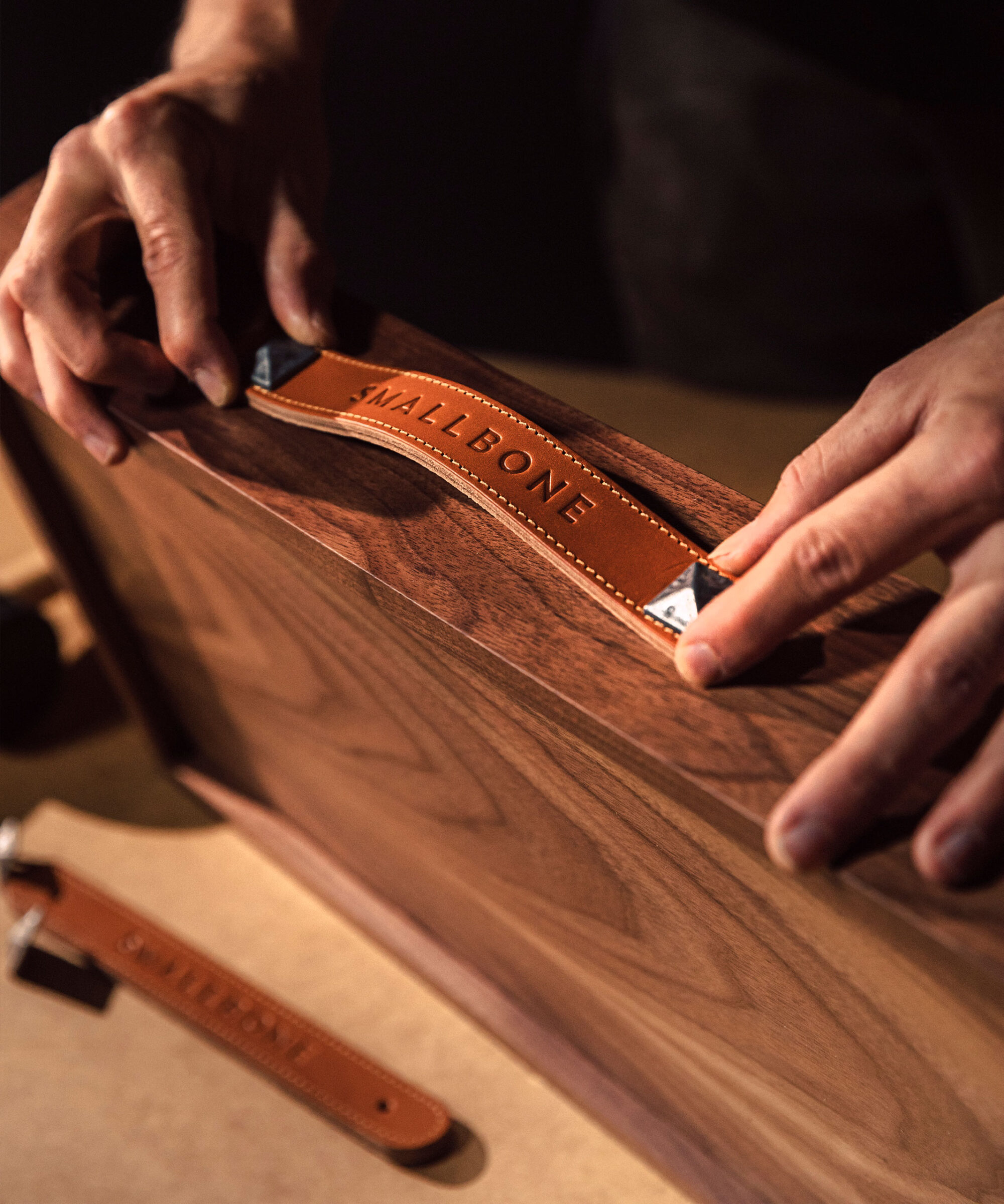a craftsman applying a Smallbone tan leather pull handle to an American walnut draw front